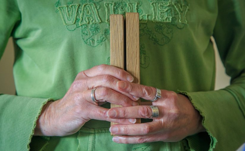 Senior hands with rings holding Zen wooden clappers, photo by Flint Sparks
